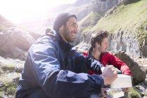 Montañeros sentado y comer comida - foto de stock