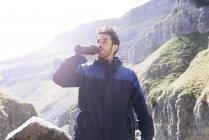 Bergsteiger-Trinkwasser aus der Flasche — Stockfoto