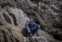 Alpinista sentado sobre las rocas en terreno accidentado - foto de stock