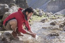 Mountaineer stopping to wash in mountain stream — Stock Photo