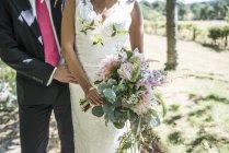 Невеста и жених с букетом цветов — стоковое фото