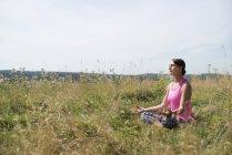 Donna in prato praticare yoga — Foto stock