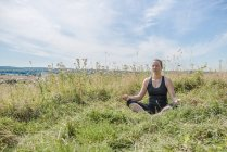 Woman in meadow practicing yoga — Stock Photo