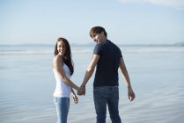 Couple walk holding hands across beach — Stock Photo