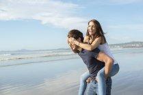 Man giving piggyback ride to female friend — Stock Photo