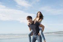Uomo che dà sulle spalle giro alla amica — Foto stock