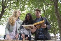 Троє друзів в книжковому кіоску — стокове фото