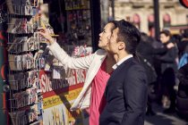Couple choosing postcards in stand — Stock Photo
