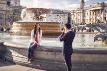 Uomo fotografare fidanzata vicino fontana — Foto stock