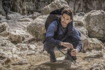 Альпинист наполняет бутылку с водой — стоковое фото