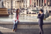 Woman on fountain edge posing for camera — Stock Photo