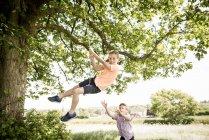 Ragazzi che giocano sull'altalena in campagna — Foto stock
