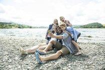 Family taking selfie on shore — Stock Photo