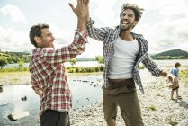 Men leaping to high five — Stock Photo