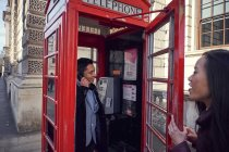 Man making phone call in telephone box — Stock Photo