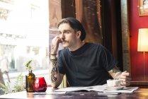 Mann sitzt am Tisch und blickt auf Fenster — Stockfoto