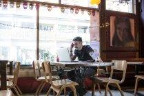 Hombre sentado en la mesa y trabajando en ordenador portátil - foto de stock