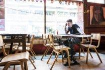 Uomo seduto a tavola e al lavoro sul computer portatile — Foto stock