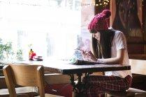Жінка сидить за столом і за допомогою смартфона — стокове фото