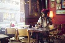 Жінка сидить за столом і, дивлячись на вікна — стокове фото