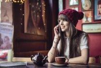 Femme assise à table et parlant au téléphone — Photo de stock