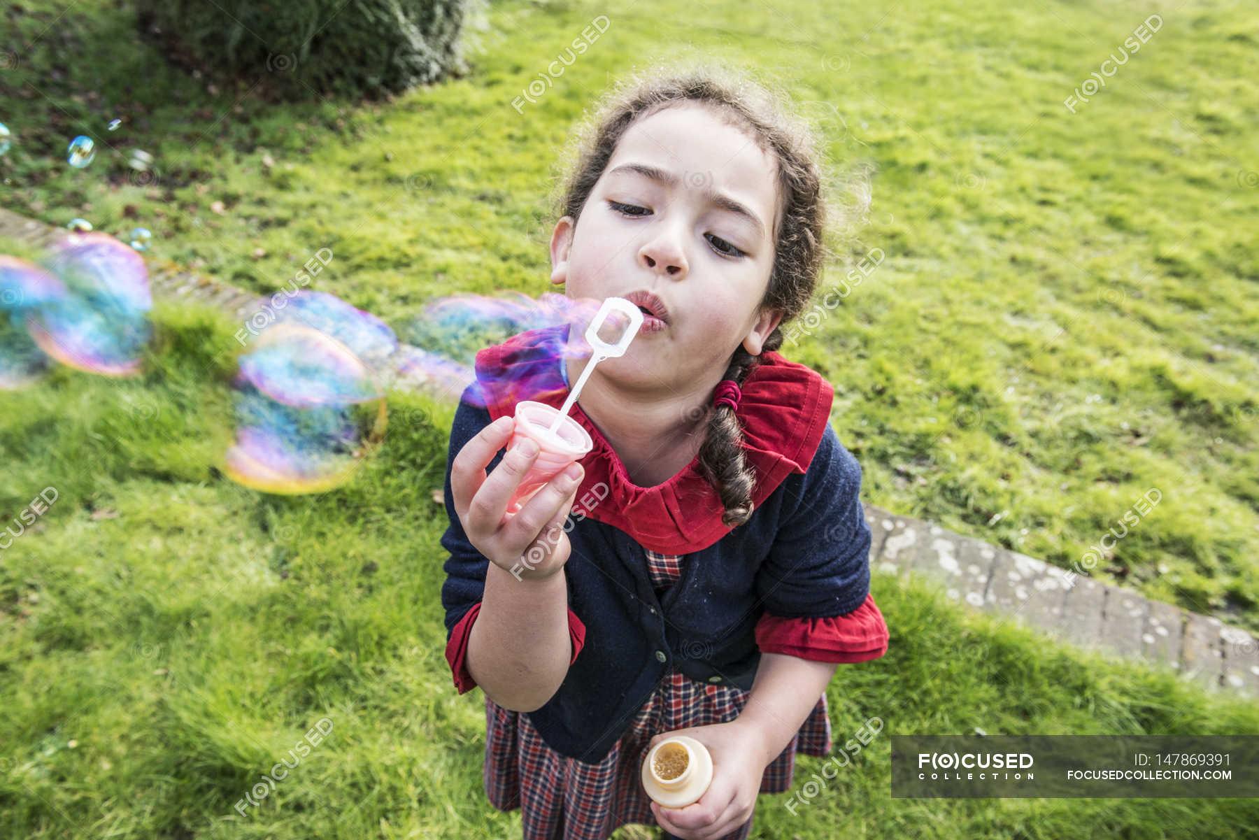 Image Of Little Girl Blowing Soap Bubbles In Backyard Garden