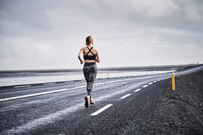 Woman running on deserted road — Stock Photo