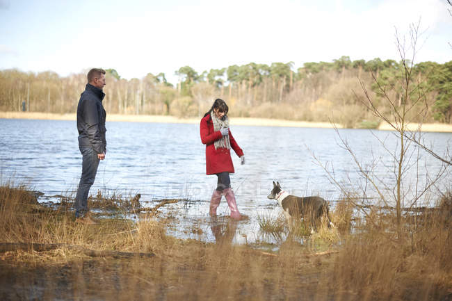 Couple on walk in woods by lake — Stock Photo