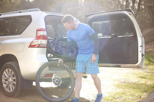 Man taking mountain bike from car trunk — Stock Photo