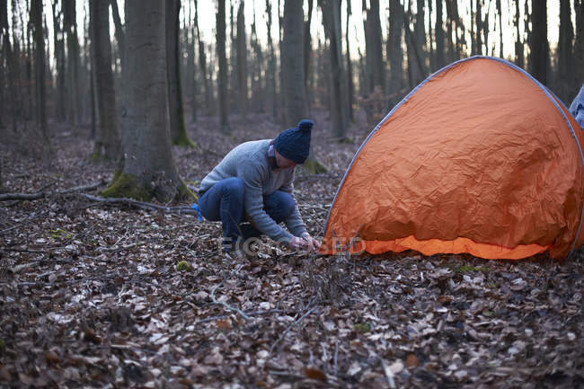 Man puts up tent in woods — Stock Photo