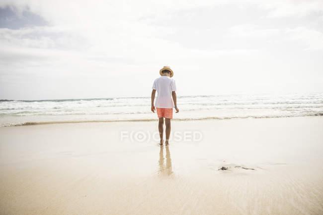 Menino andando na praia — Fotografia de Stock