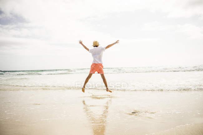 Garçon sauter sur la plage — Photo de stock