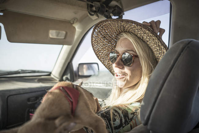 Female surfer sitting in car with dog — Stock Photo