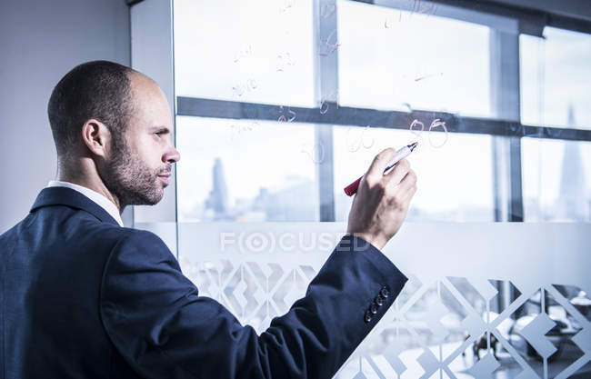 Businessman writing numbers on glass — Stock Photo