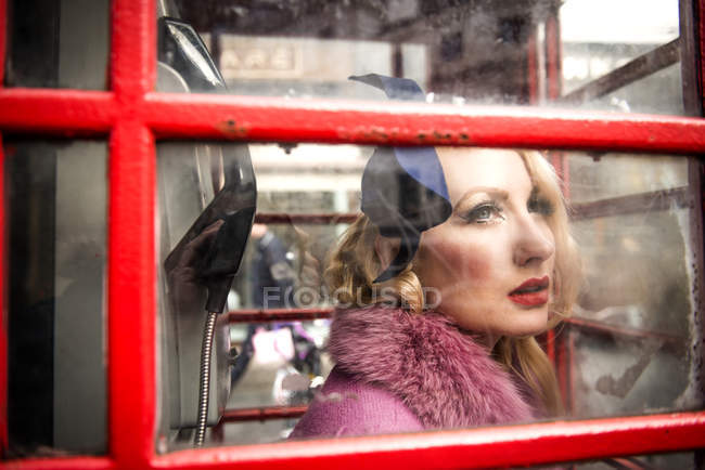 Woman standing in telephone kiosk on London — Stock Photo