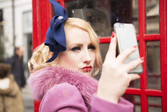 Жінка, беручи selfie за межами телефон кіоску — стокове фото