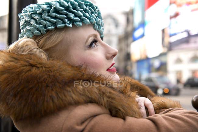 Mujer de pie por una verja en la entrada a la estación de metro - foto de stock