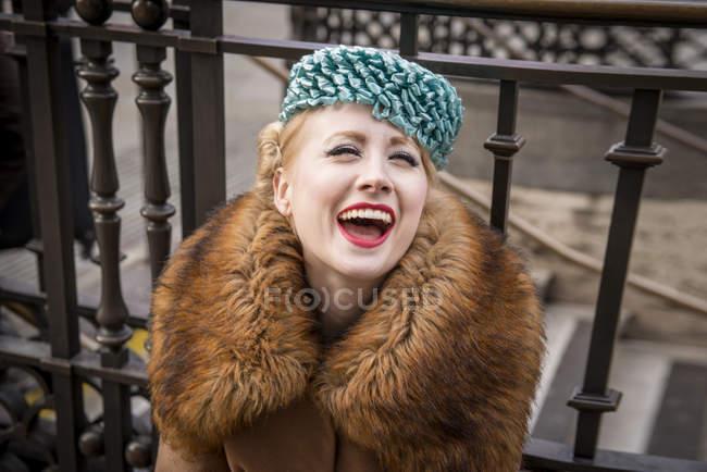 Mujer sentada riéndose por una verja - foto de stock