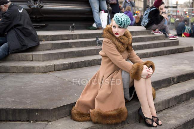 Donna che si siede dalla statua di Eros — Foto stock