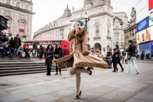 Woman twirling around by statue of Eros — Stock Photo
