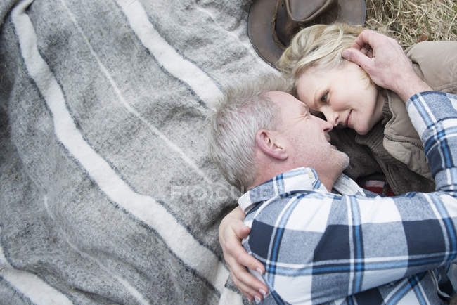 Senior couple cuddling together on blanket — Stock Photo