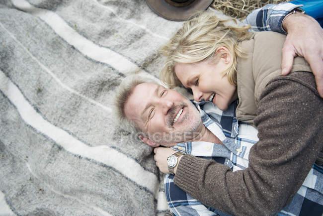 Senior Couple Cuddling Together On Blanket Stock Photo