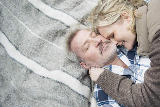 Старшая пара обнимается на одеяле — стоковое фото