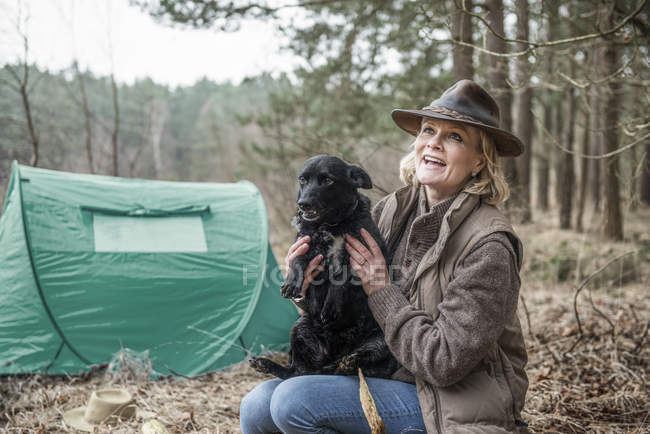 Lady sitting with dog enjoying wilderness — Stock Photo