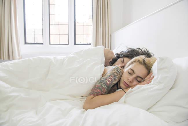 Tattooed couple sleeping in bed — Stock Photo