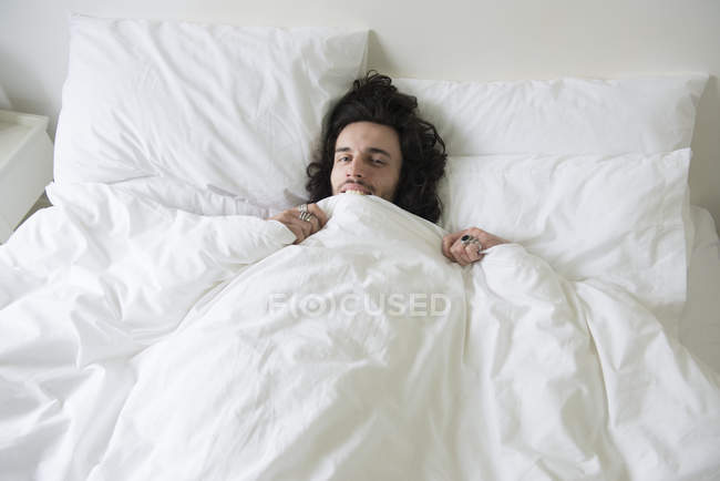 Man lying in bed — Stock Photo