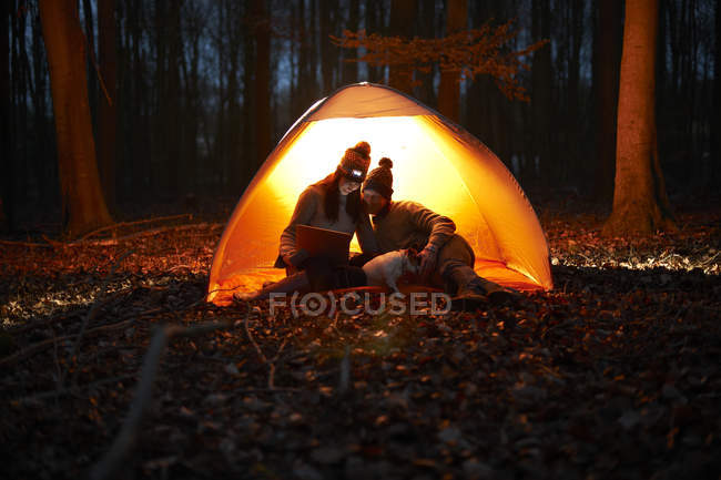Couple sit in tent at night — Stock Photo