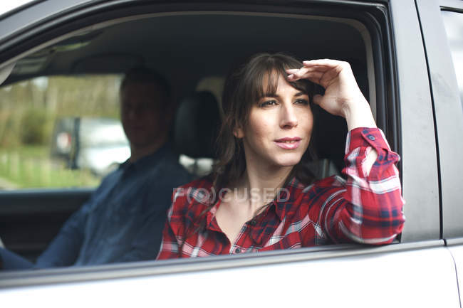 Woman looks wistfully out of car window — Stock Photo