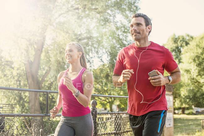 Man and woman jogging through park — Stock Photo