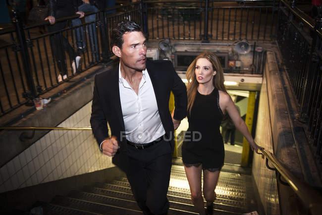 Пара, идущая вверх по лестнице по городу — стоковое фото